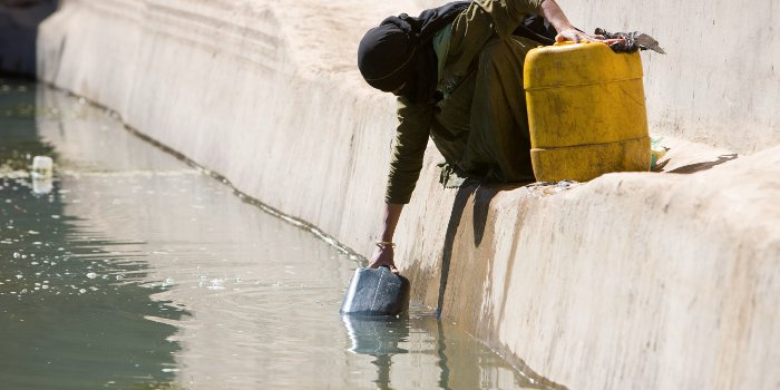 Woman fetches water from polluted source