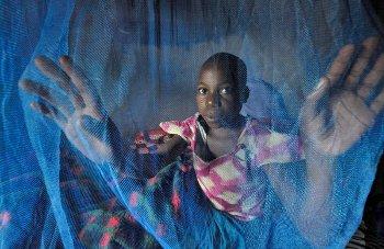 Girl with mosquito net in Dundube Kadambo, Malawi