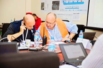 Frederik Copper, WHO's exercise controller discusses details with communications controller Denis Charles