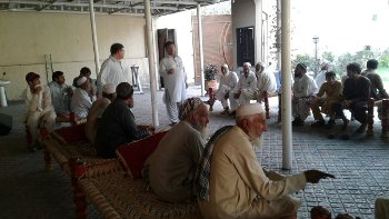 Old and young men engaged in dialogue, Haripur