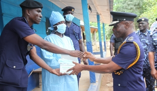 The Commissioner for Customs at the Ghana Revenue Authority (right) hands over protective equipment to GRA customs officers at a visit to a border crossing in November 2014.