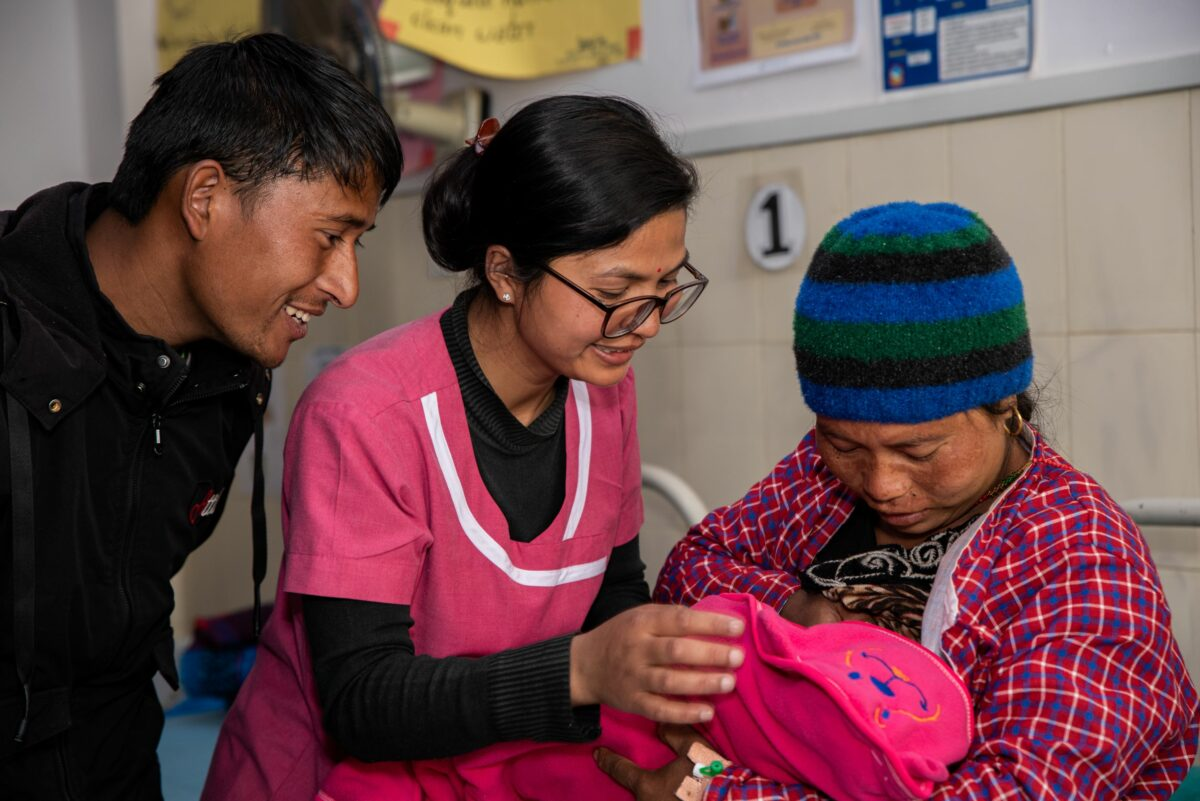 A midwifery student on clinical placement helps a new mother establish breastfeeding