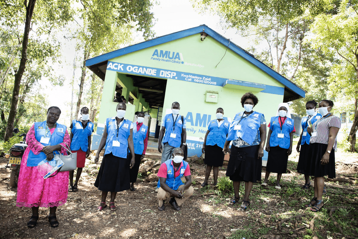 Community health workers in Kenya gather outside a local health facility. The community health workers have been fighting malaria in their community – now they are on the front lines of the fight against COVID-19.
