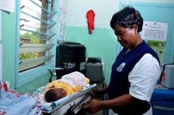 Nurse weighs new born baby in Kisumu clinic