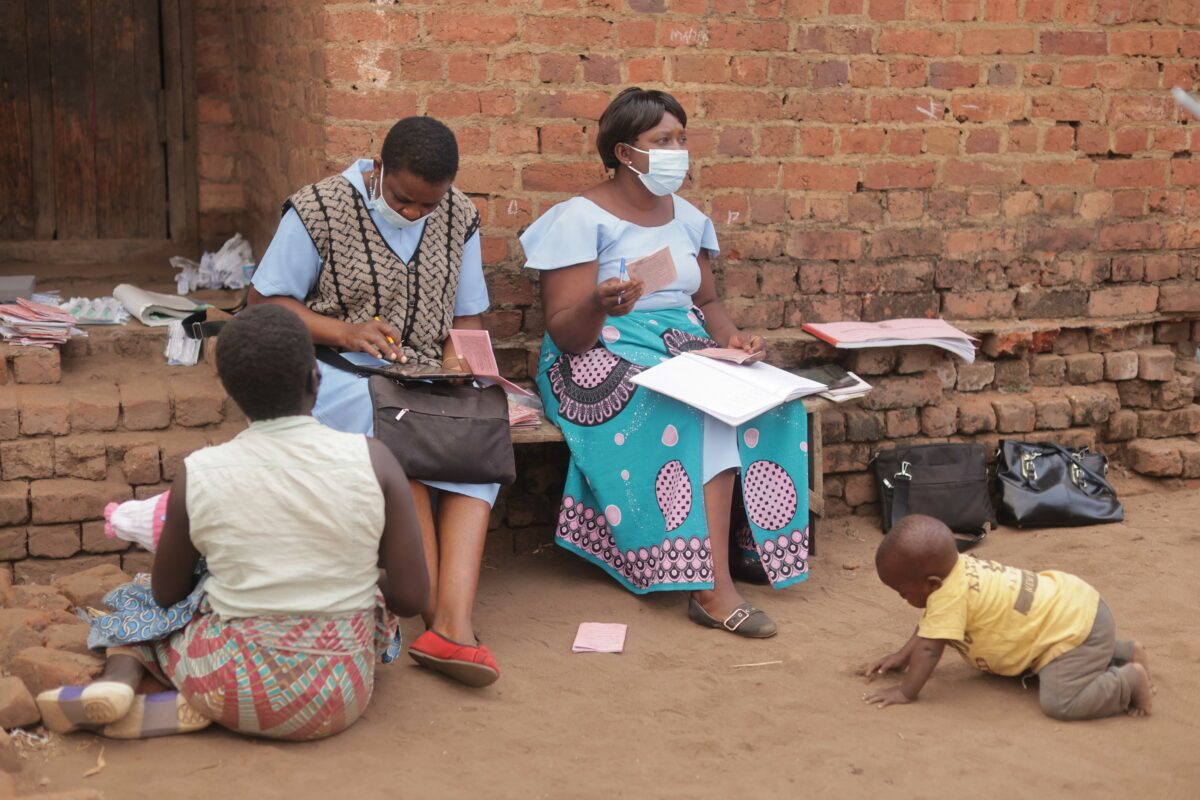 A nurse records a child's vaccination details on a tablet at an outreach clinic